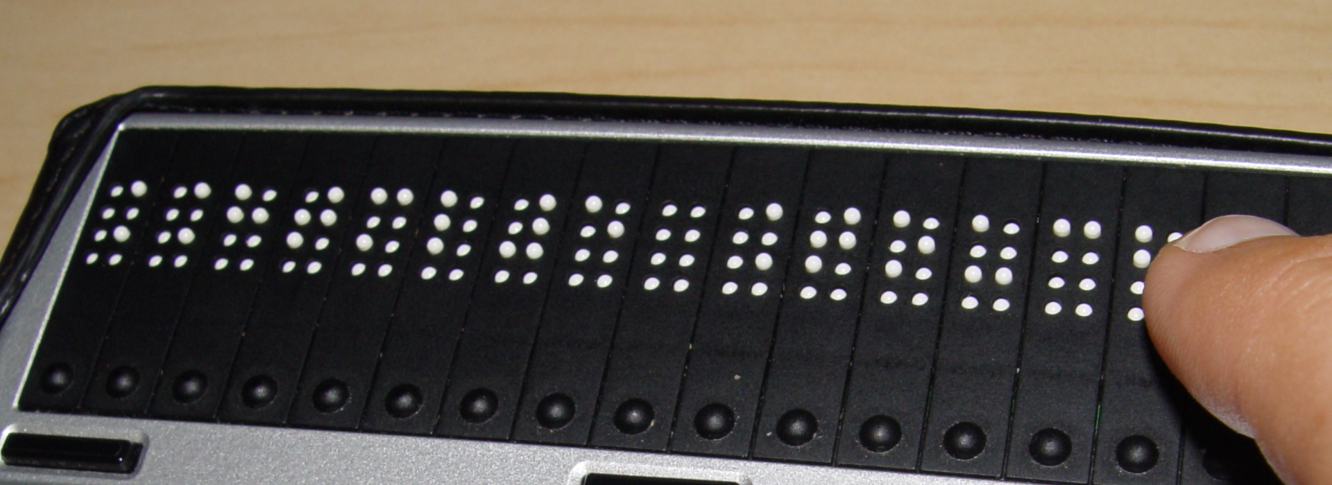 Foto dedo leyendo braille digital.